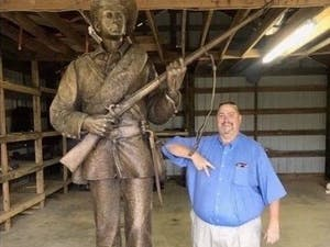 "Kevin Stone, commander of the Sons of Confederate Veterans' North Carolina chapter, poses next to Silent Sam after suing and immediately settling with the UNC System and Board of Governors, a deal that gave the group possession of the Confederate monument and $2.5 million in UNC System money for its ""preservation and benefit."" Photo courtesy of SCV members."