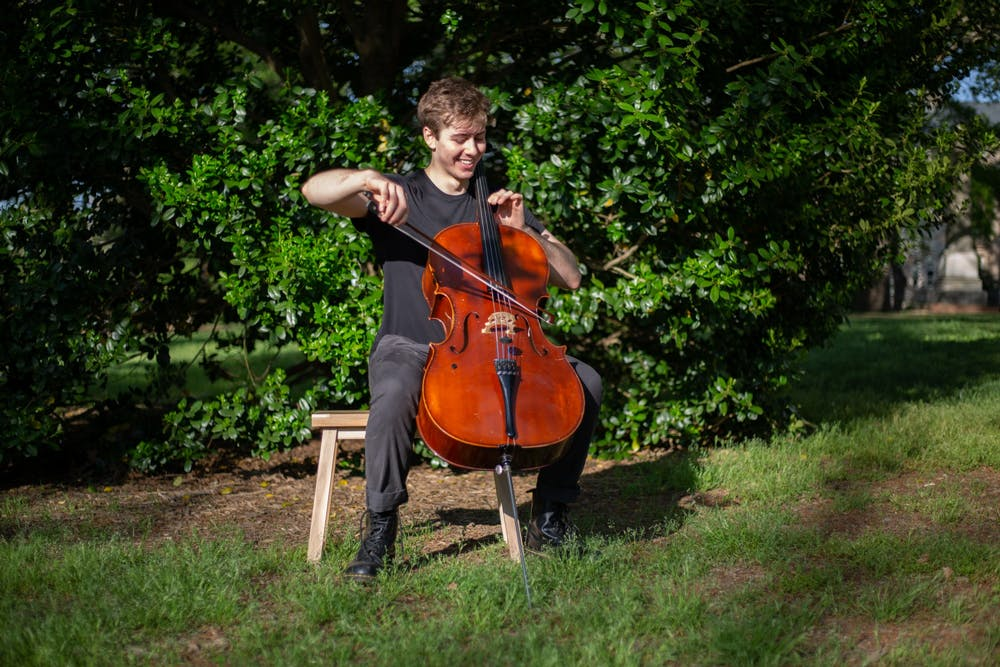 Benjamin Carter, a junior psychology major, plays his cello in McCorkle Place on Sunday, Apr. 11, 2021. Carter just released his album, Coming Out of It.
