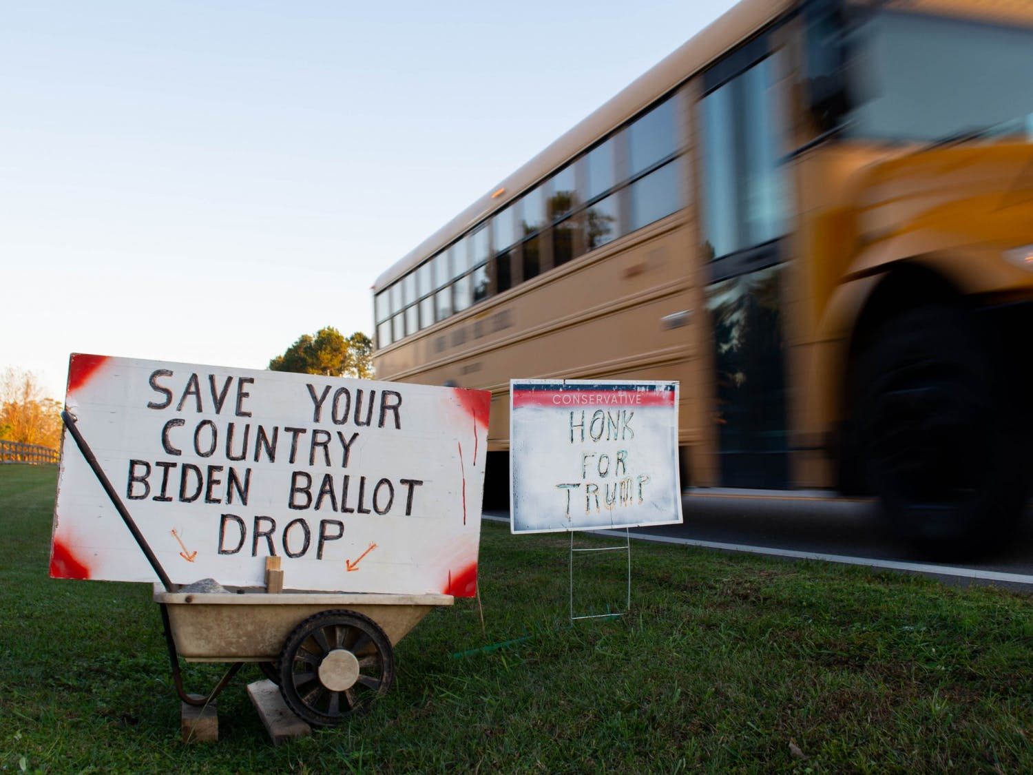 "A school bus passes by election signs in the yard of a Johnson County resident on Monday, Nov. 2, 2020. One sign encourages voters to ""save their country"" by throwing away ballots for Biden."