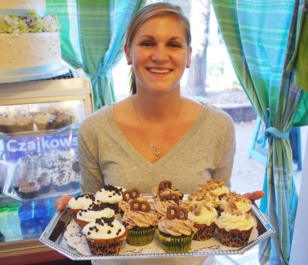 Local cupcake store Sugarland displays some of their fall cupcakesUNC exercise science student and Sugarland employee, Carley Brown displays some fall cupcakes (from left to right): Pumpkin Chocolate Chip, Oktoberfest, and Sweet Potato Praline
