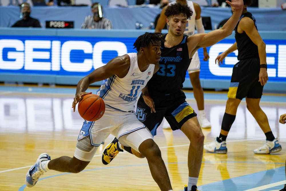 UNC first year center Day'Ron Sharpe (11) attempts to shoot around Marquette first year forward Dawson Garcia (33) during a game in the Smith Center on Wednesday, Feb. 24, 202. UNC lost to Marquette 83-70.