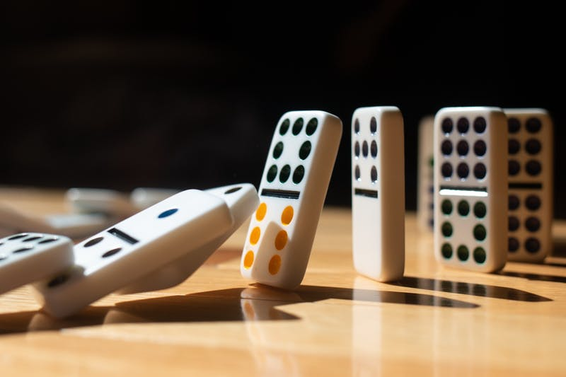 A DTH Photo Illustration. A row of dominoes falls over one by one.