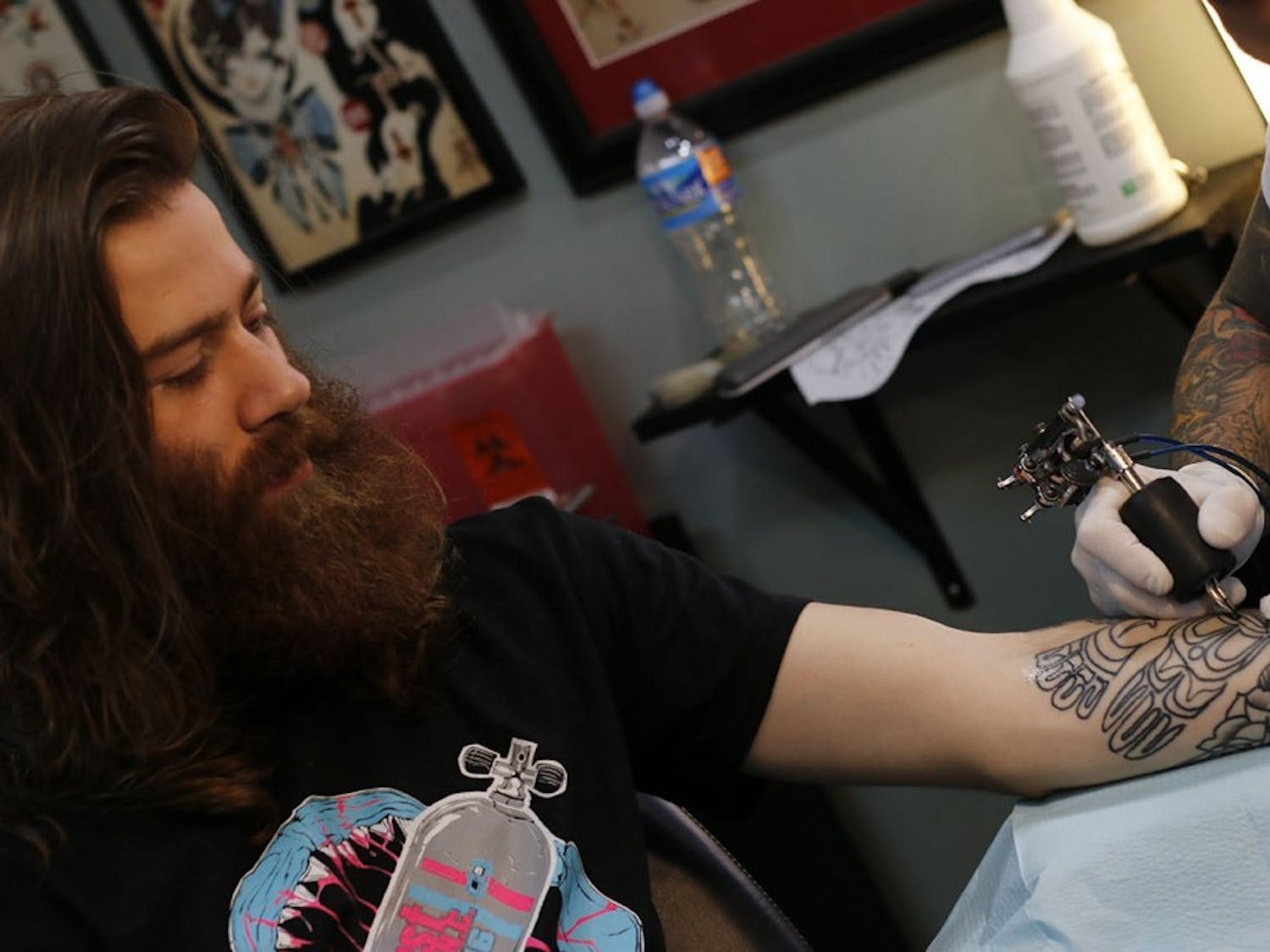 Hayden Fitzgerald watches as Mike Wheeler works on his tattoo.