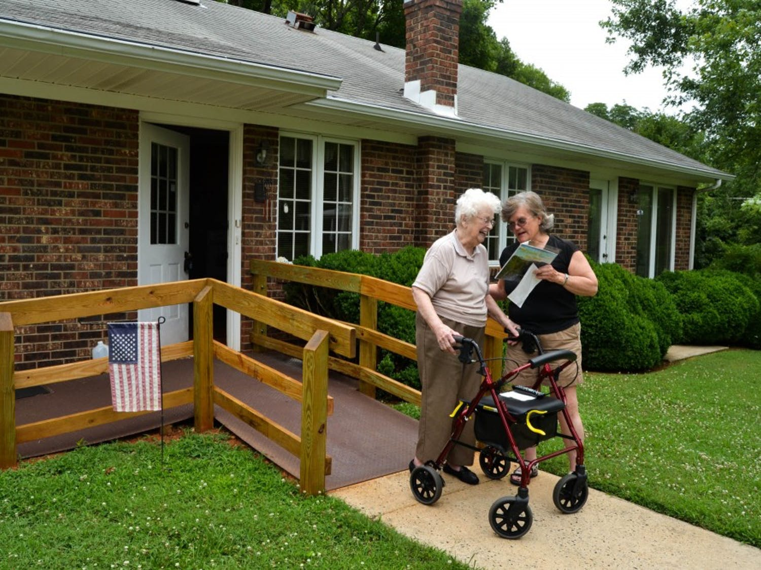 Kacky Hammon visits with Doris Ray at the bottom of her ramp built by Handy Helpers.