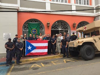 Jennifer Kelly and her team in Puerto Rico pose with Puerto Rican flag. They arrived in Puerto Rico to provide medical assistance and set up a clinic. Photo courtesy of Kelly.
