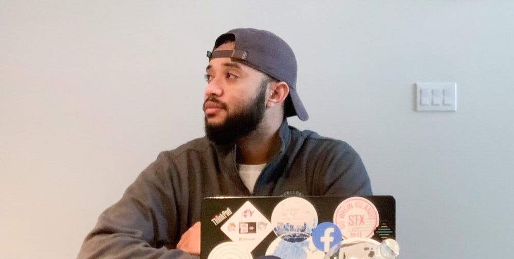 Former UNC student, Charlie Helms poses for a virtual portrait with his old college laptop in his Seattle apartment on Jan. 27, 2021. Helms co-founded Black in Technology, an organization dedicated to helping students of color in Computer Science.