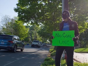 Margie Muenzer holds up a sign as cars drive by outside of UNC's coal plant on Friday, Apr. 23, 2021.
