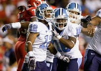 UNC?s Charles Brown (12) and Kendric Burney (16) celebrate Brown?s interception in the second quarter during North Carolina?s 44-12 win.