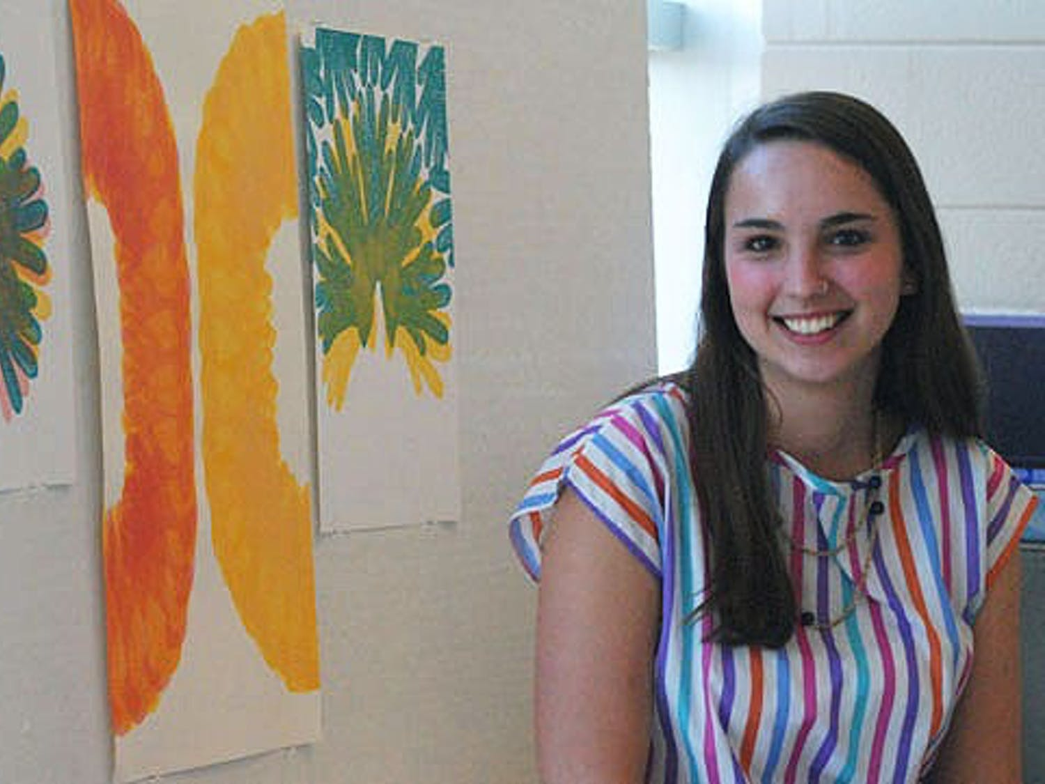Kaitlin Knapp, Fine Art major with a focus in Art History, displays screen prints in Hanes Art Center. Ali Halperin shows her piece on materialism using screenshots from the program Hoarders.