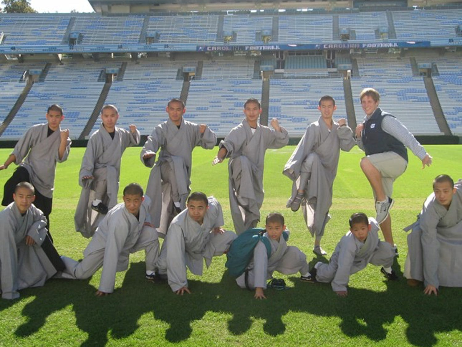 """Junior Patrick Spaugh poses with the Shaolin Monks of """"Sutra"""" as they tour UNC, one of two spots in which """"Sutra"""" will perform in the U.S."""