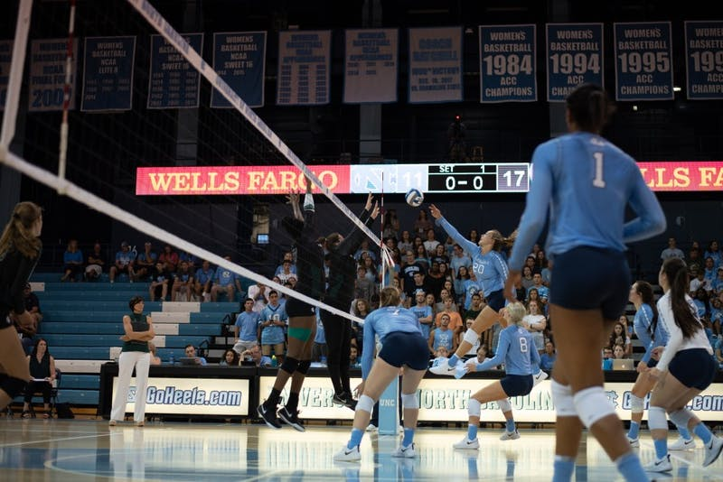 Outside hitter Ava Bell (20) tries to hit around two outstretched defenders during a 3-1 loss to Michigan State on Sept. 1 in Chapel Hill.