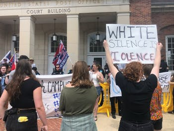 Anti-Confederate demonstrators held up signs protesting the Confederate supporters and police brutality in front of the pro-Confederates.