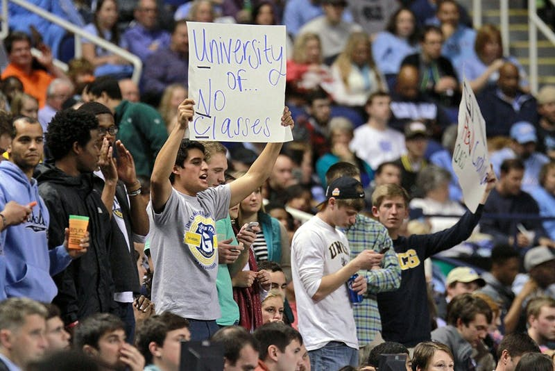 UNC-Greensboro fans held signs mocking UNC's athletic-academic scandal.
