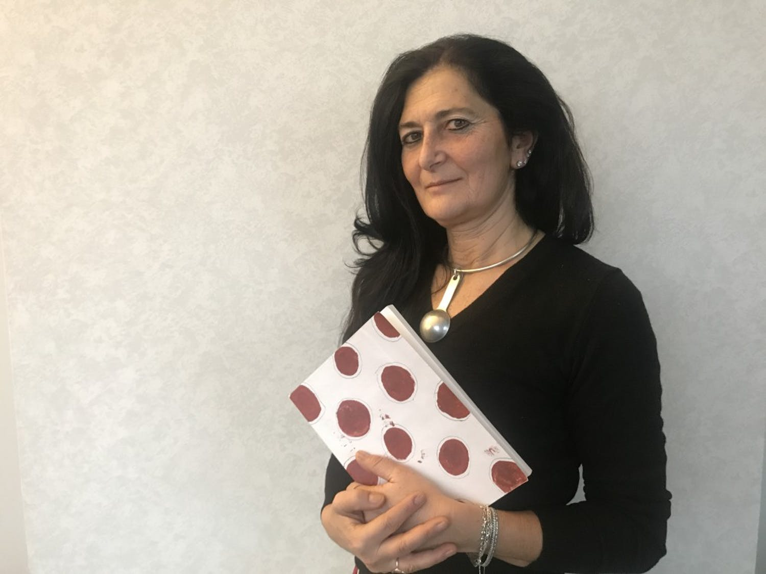 Manuela De Leonardis poses with her book 'The Blood of Women: Traces of Red on White Cloth' after her lecture at the FedEx Global Education Center.