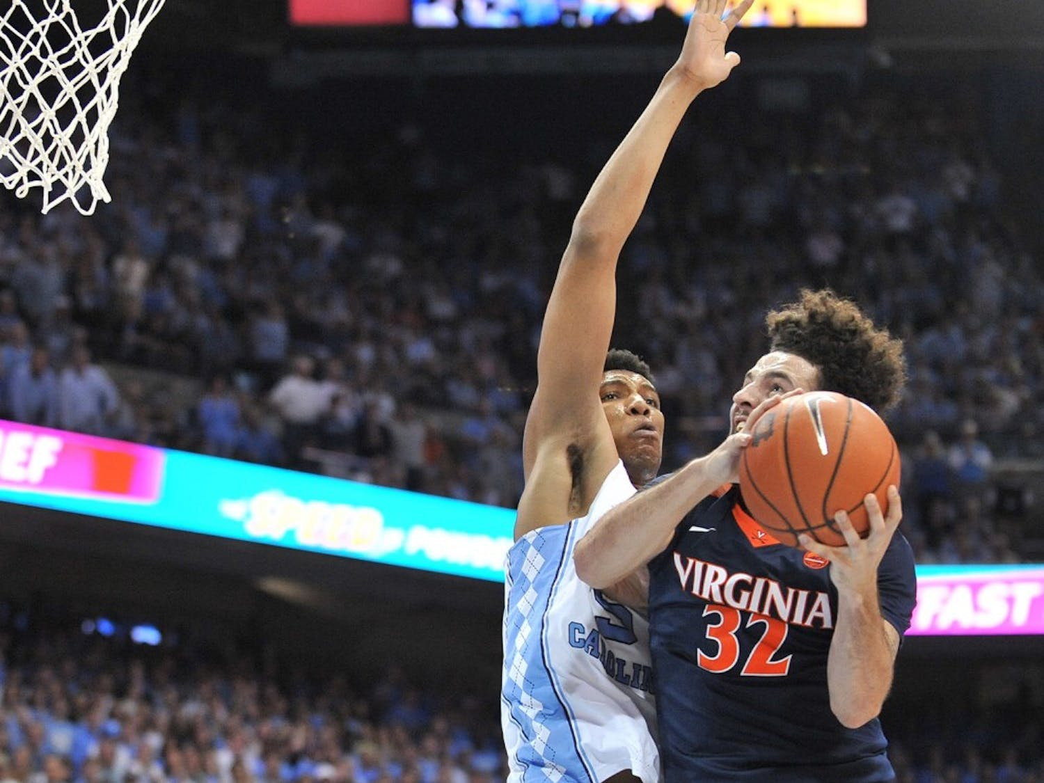 No. 10 North Carolina forward Tony Bradley (5) reaches up in an attempt to block No. 14 Virginia guard London Perrantes (32) during Saturday night's game in the Smith Center.
