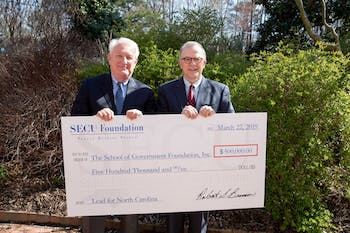 Bob Brinson (left), SECU Foundation Board chairperson, presents a $500,000 check to Mike Smith (right), dean of the UNC School of Government, to support the Lead for North Carolina program. Photo by Ben McKeown.