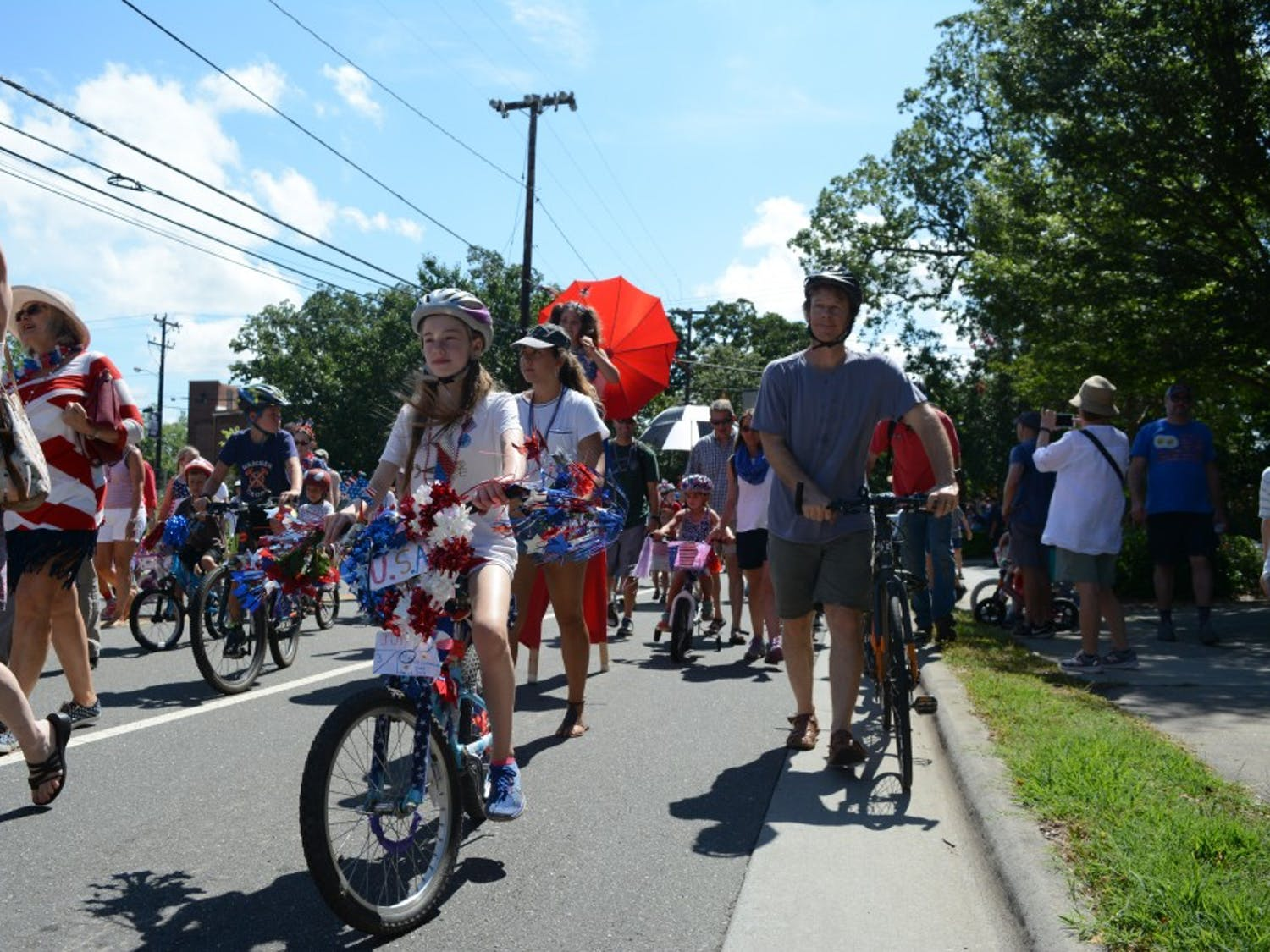 Rose Kohout from Carrboro rides her first place-winning decorated bicycle down Weaver Street during Carrboro's Fourth of July Parade.