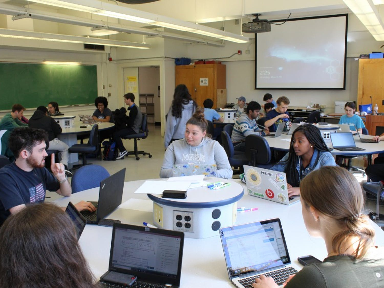 Students prepare for class in Phillips 208 on Monday, March 18, 2019. This is one of five classrooms considered a 'Studio Classroom' and just one type of classroom in Carolina's Flexible Learning Spaces Initiative. The Initiative's purpose is to improve student-focused interaction through the modernization of classrooms.