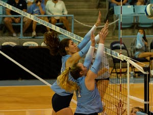 UNC senior middle hitter Amanda Phegley (7) and sophomore middle hitter Kaya Merkler (14) block a hit during a home volleyball game against the University of Virginia on Sept. 26 in Carmichael Arena.