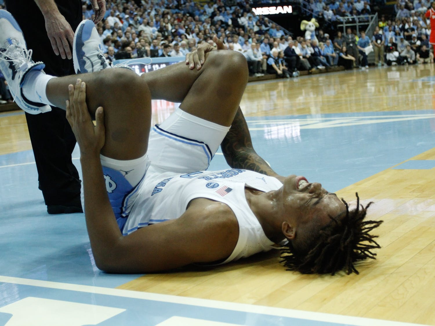Freshman forward Armando Bacot (5) lies injured on the ground.