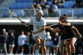 UNC senior attacker Katie Hoeg (8) keeps the ball from an opposing player during the game against Maryland at Dorrance Field on Saturday, Feb. 22, 2020. No 1. UNC won against No 4. Maryland 19-6.