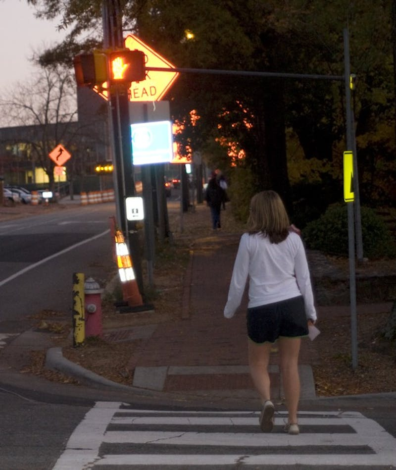 "Freshman Anna van Venrooy crosses in front of a ""do not walk"" signal on campus.  UNC is planning to increase enforcement of jaywalking."