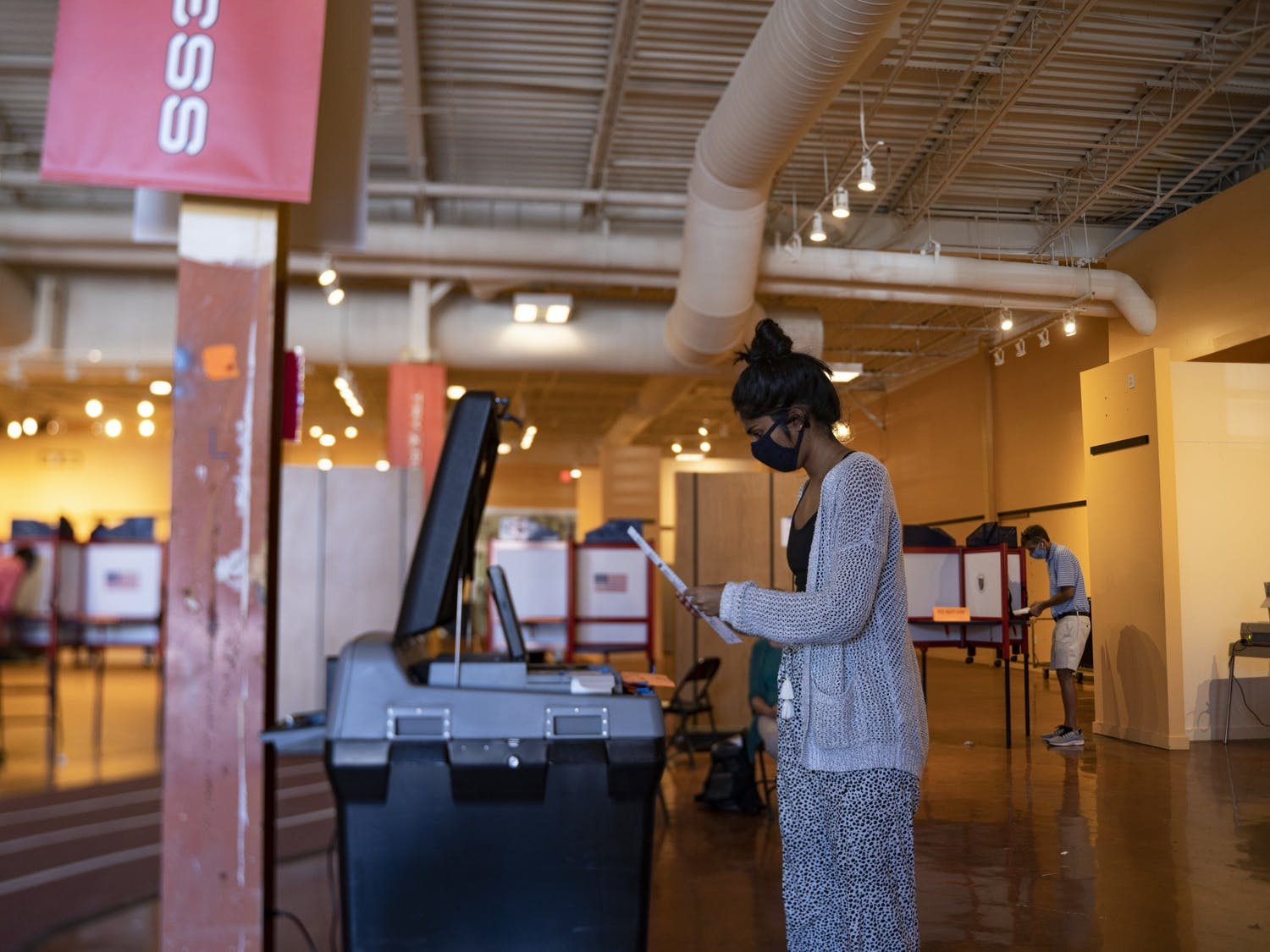Nisha Iyer turns in her ballot at the early voting site at University Place on Tuesday, Oct. 20, 2020.