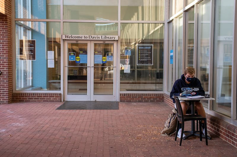 A student does homework outside of Davis Library on Sunday, Oct. 18, 2020. UNC Libraries are creating a new delivery-by-mail service so that remote students can use the library's resources.