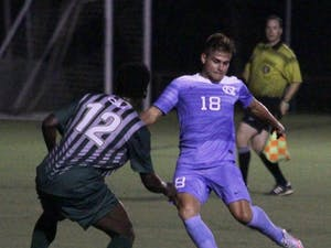 UNC forward Alan Winn (18) takes a shot against William & Mary on Wednesday night at WakeMed Soccer Park.