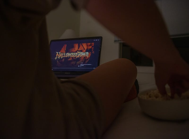 """DTH Photo Illustration. A student watches """"Halloweentown."""" With COVID-19 forcing students to get creative with their Halloween celebrations, many are opting to stay in and watch spooky movies and TV shows."""
