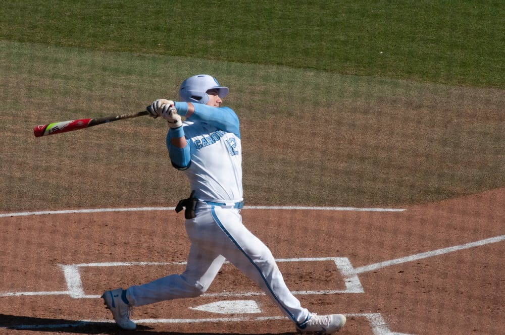 <p>UNC first-year outfielder Will Stewart (12) swings at a pitch during UNC's 7-4 win over James Madison at Boshamer Stadium, Feb. 20, 2021.</p>