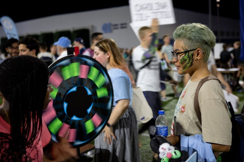 Jade Hampton, a senior information and library science major, spins a wheel for a prize during Fallfest on Hooker Fields on the evening of Sunday, August 18 2019.