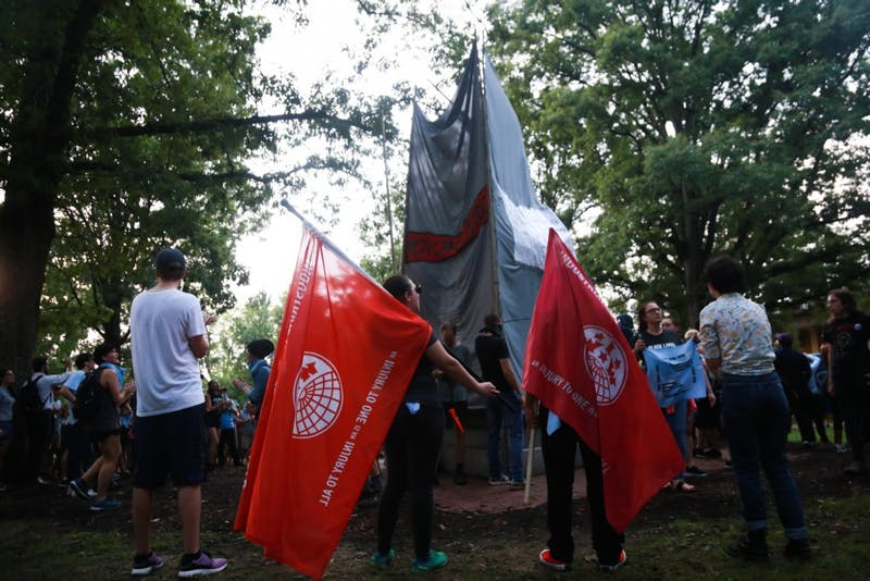 Rally attendees hold flags as other protesters tie banners around Silent Sam.