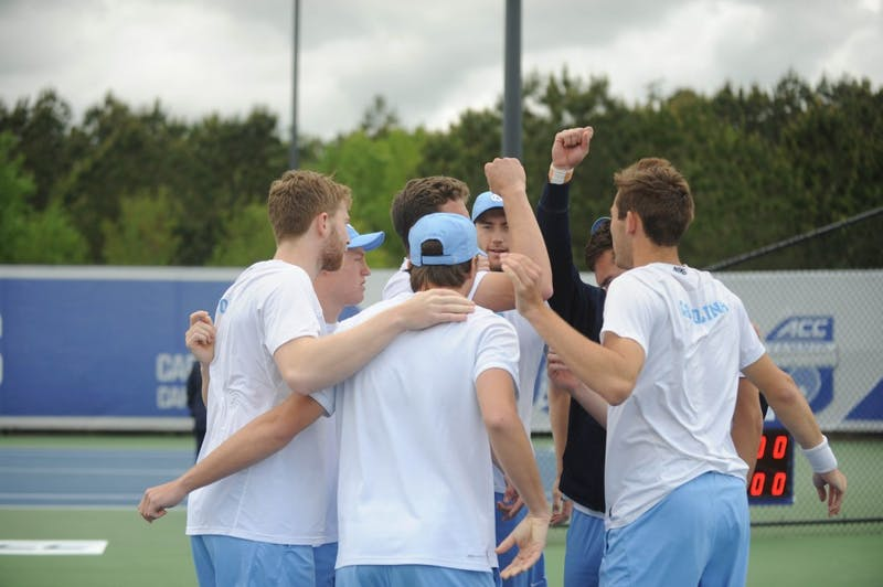 The UNC men's tennis team huddles together at the ACC tournament semifinals. UNC played against Virginia and lost 3-4.
