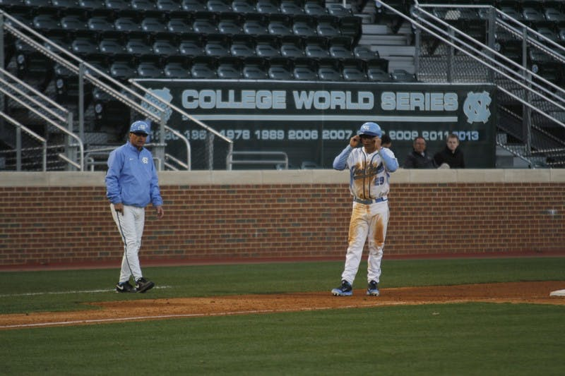 North Carolina head coach Mike Fox talks to outfielder Tyler Ramirez at third base in Tuesday's win over Appalachian State.