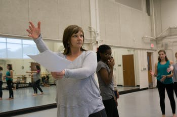Heather Tatreau, a Teaching Assistant Professor at UNC in the Exercise and Sports Science department, demonstrates a dance position for her students in Intermediate Modern Dance Technique while teaching the choreography for 19th amendment anniversary project at the Woolen Gymnasium Dance Studio on Thursday, Nov. 14, 2019.