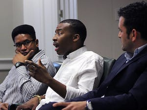 """Osiris Rankin, a senior psychology major, Darius Whitney, a senior political science major, and Dr. Juan Carrillo, an assistant professor in the UNC School of Education, discuss their place in the university setting and the challenges they have faced as minority males at a Carolina Millennial Scholars Program's event entitled """"The [Mis]sed Education of the Minority Male"""" Thursday evening in Wilson Library."""