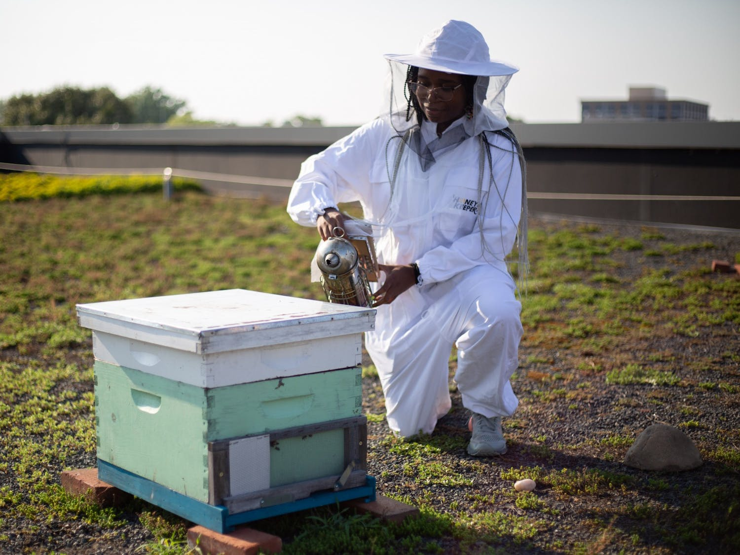 Junior biochemistry major Adrienne Lambert demonstrates how to use a smoker on a beehive on Monday, Aug. 23, 2021. Lambert is the president of the Carolina Beekeeping Club.