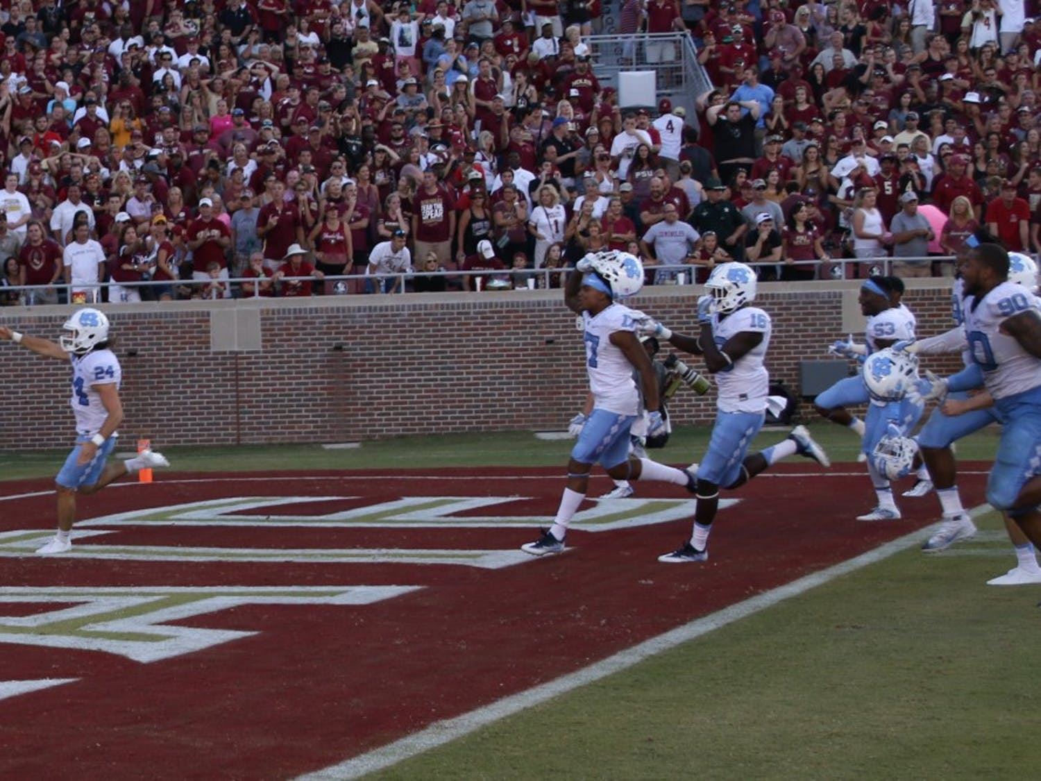 "UNC kicker Nick Weiler (24) imitates the Florida State ""Tomahawk Chop"" as he celebrates kicking a career high 54-yard field goal as time expired to lift UNC over Florida State."