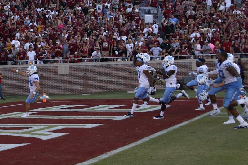 """UNC kicker Nick Weiler (24) imitates the Florida State """"Tomahawk Chop"""" as he celebrates kicking a career high 54-yard field goal as time expired to lift UNC over Florida State."""