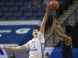 North Carolina Walker Kessler (13) blocks a shot by Notre Dame's Juwan Durham (11) in the second half on Wednesday, March 10, 2021 during the ACC Tournament at the Greensboro Coliseum in Greensboro, N.C. Photo courtesy of Robert Willett.