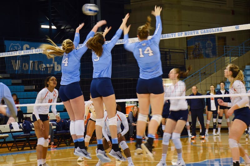 North Carolina hitters Taylor Borup (4), Beth Nordhorn (3) and Madison Laufenberg (14) elevate for a block against Syracuse on Sunday afternoon in Carmichael Arena.