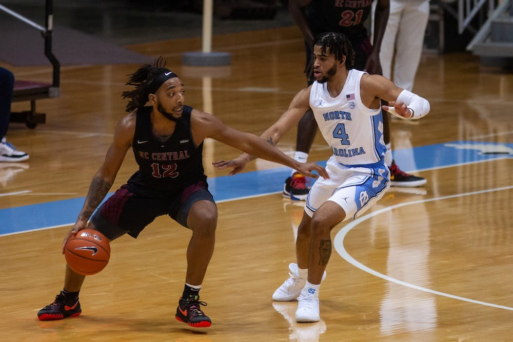 <p>UNC's first year guard RJ Davis (4) defends against N.C. Central's senior guard Jordan Perkins (12) during a game in the Smith Center on Saturday, Dec. 12, 2020. UNC beat N.C. Central 73-67.</p>