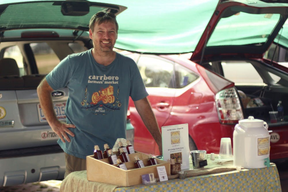 <p>Marty Hanks, owner of Just Bee Apiary, sells his honey producst at the Carrboro Farmer's Market on Wednesday afternoon.</p>