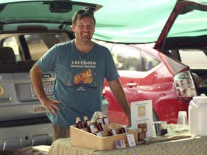 Marty Hanks, owner of Just Bee Apiary, sells his honey producst at the Carrboro Farmer's Market on Wednesday afternoon.