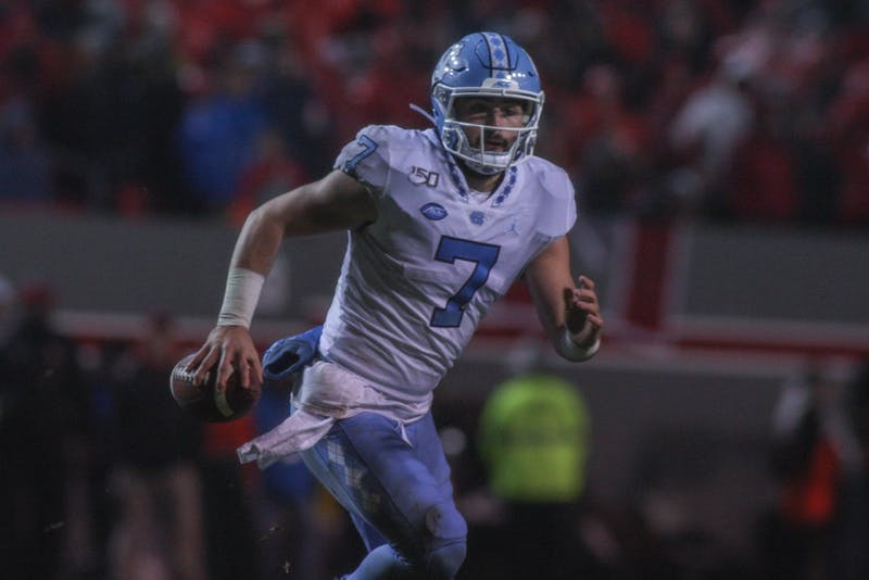 UNC first-year quarterback Sam Howell (7) runs with the ball in Carter-Finley Stadium on Saturday, Nov. 30, 2019. UNC defeated NC State 41-10.