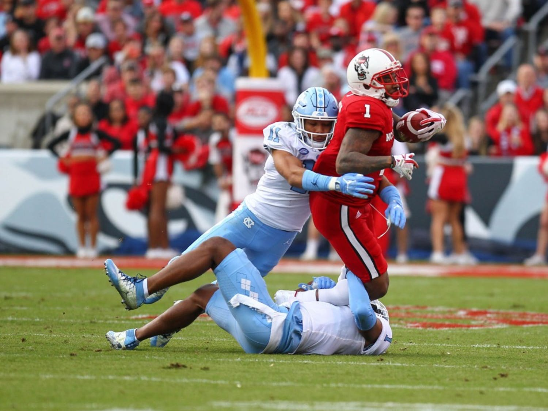 North Carolina safety Myles Wolfolk (11) tackles N.C. State all-purpose back Jaylen Samuels (1) on Nov. 25 in Raleigh,