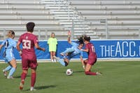 Alex Kimball (47), a redshirt senior midfielder for the Tar Heels' women's soccer team, takes a hard tackle from a defender during the 2018 ACC Championship game against Florida State on Sunday, Nov. 4.