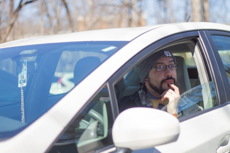 """Logan Brackett, manager for the UNC Department of Romance Studies, peers out of his car as someone explains the new five-year parking plan on Stadium Dr. on Wednesday, March 6, 2019. The plan includes provisions for weeknight parking permits, fee increases and new rules to generate revenue. """"It seems like a nickel and dime approach for fees,"""" he said. """"Students don't seem like the main beneficiaries here, so it seems odd to charge them."""""""