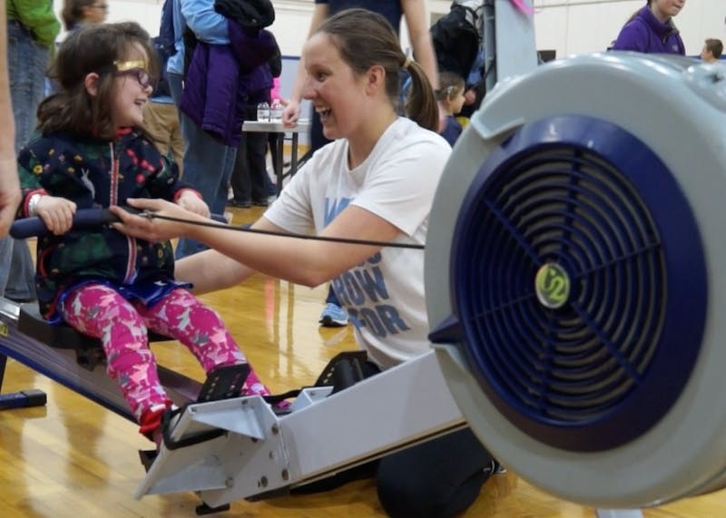 Caroline Young, who is on UNC's women's rowing team, teaches a young girl how to row during National Girls and Women in Sports Day hosted at UNC.